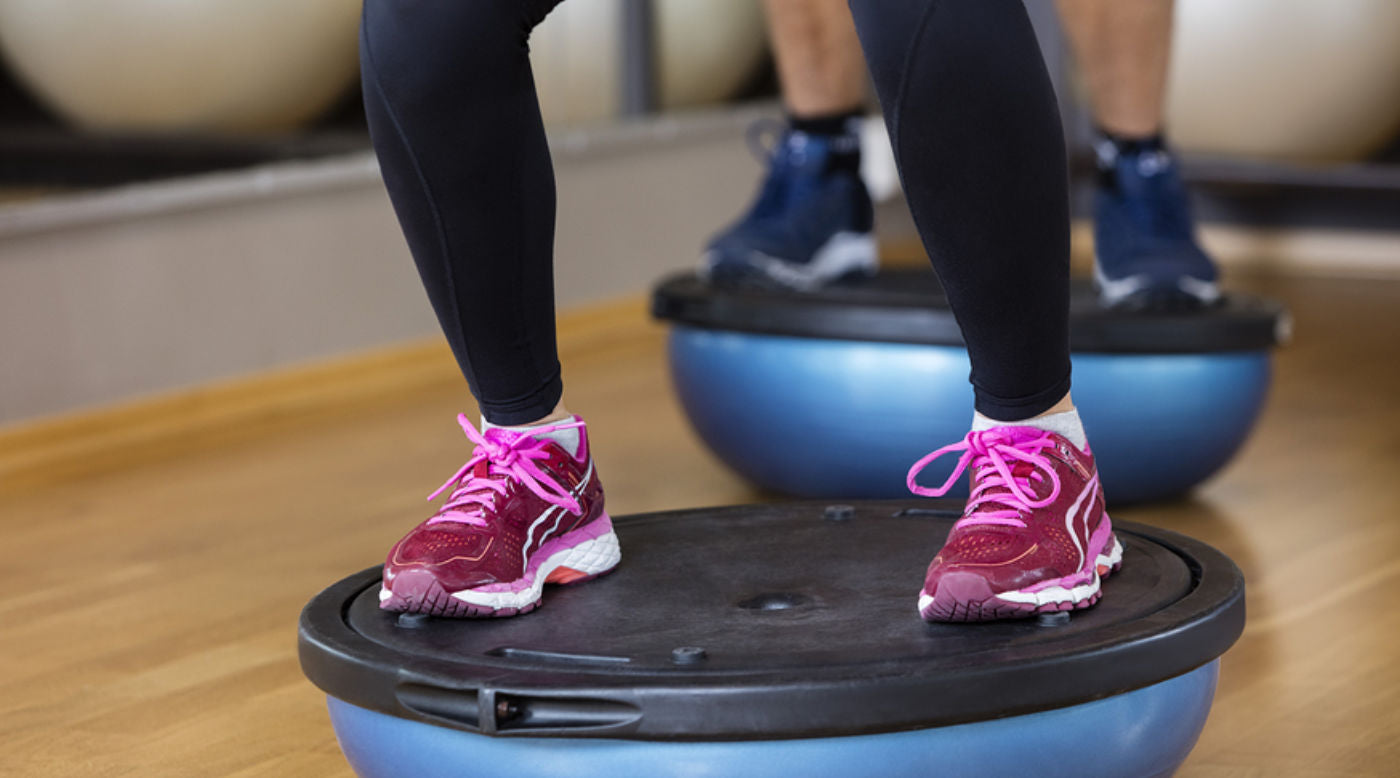 legs of woman working out on bosu ball