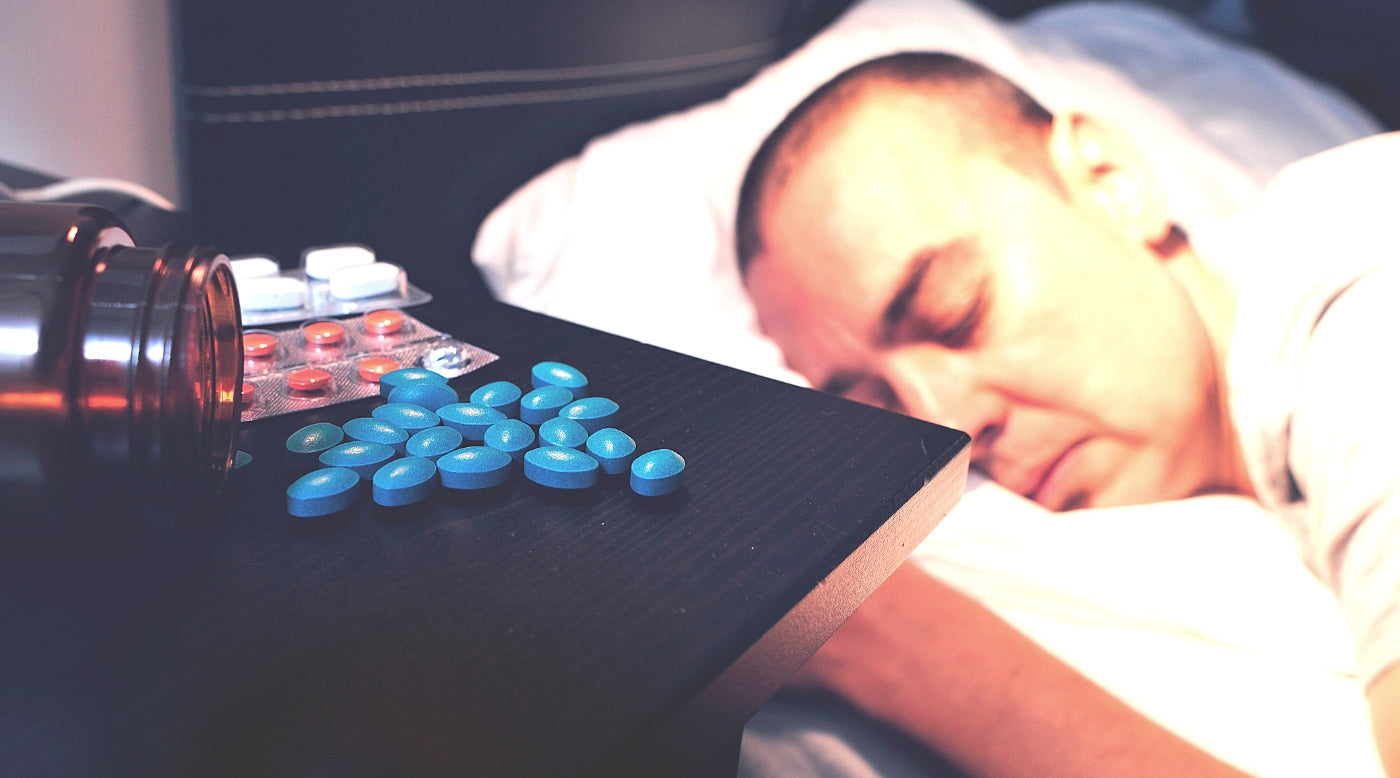 man sleeping next to pills on nightstand