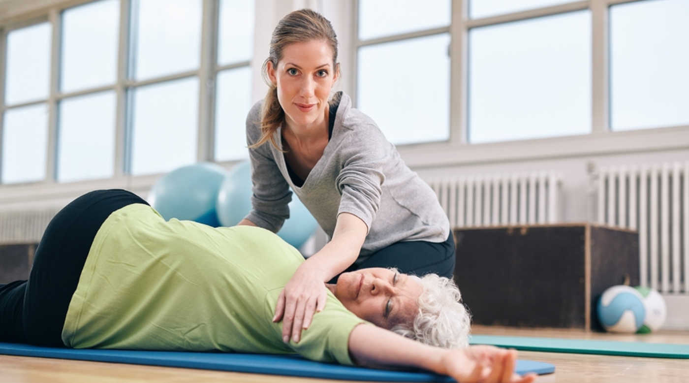 senior woman stretching with trainer