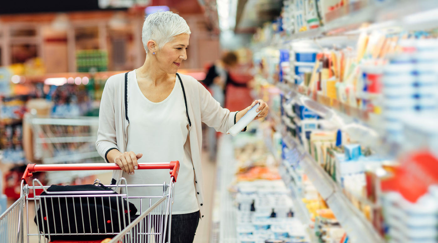 older woman reading food label at grocery store