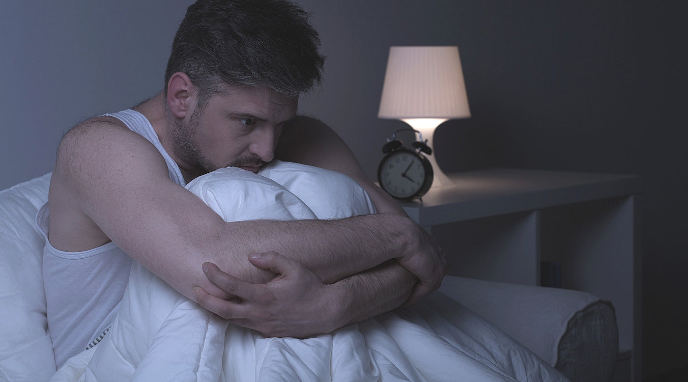 Man in bed having trouble sleeping