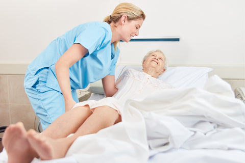 Carer changing the bed for elderly person