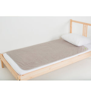 Sand large-sized PeapodMat waterproof bedding protector lying on a single bed.