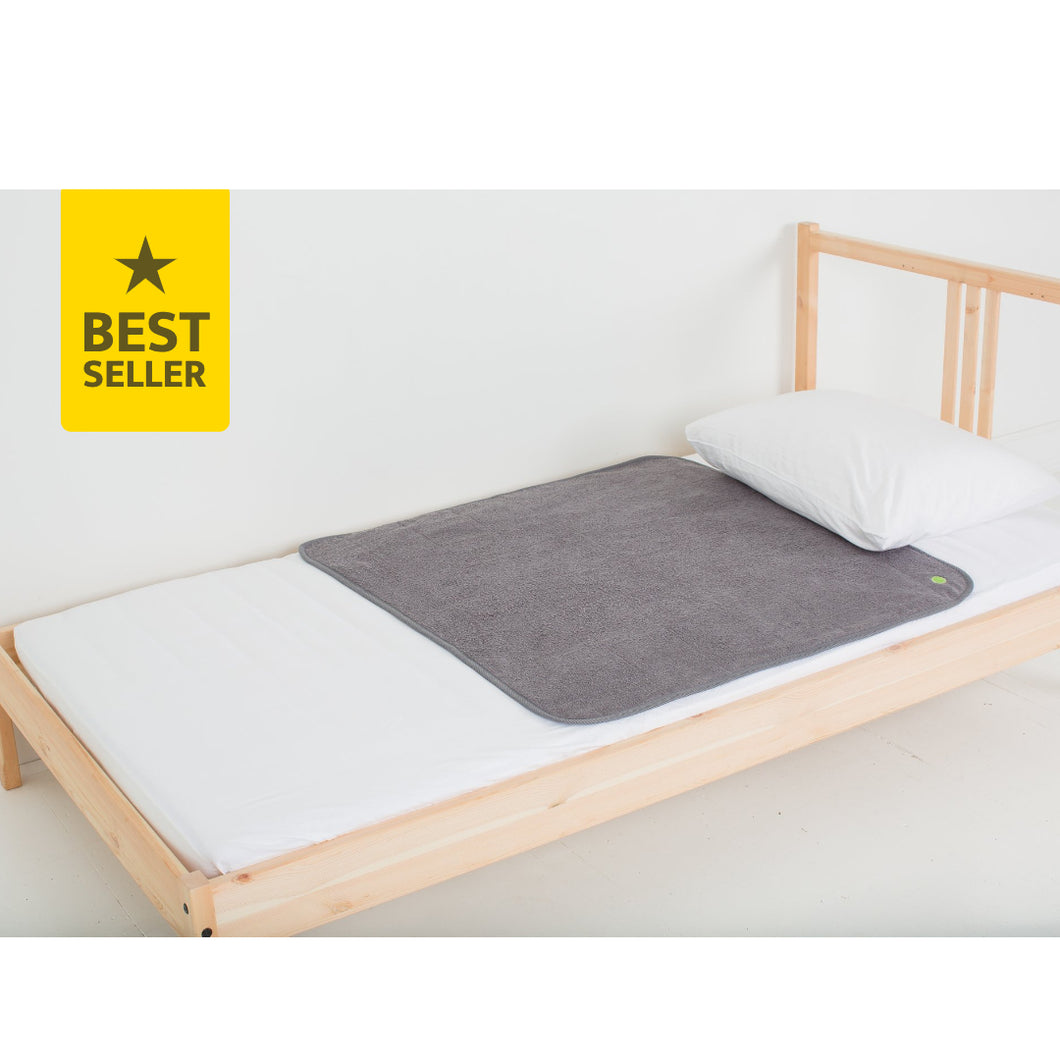 Grey medium-sized PeapodMat waterproof mattress protector lying on a single bed.