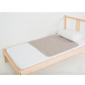 Sand medium-sized PeapodMat waterproof bed protector lying on a single bed.