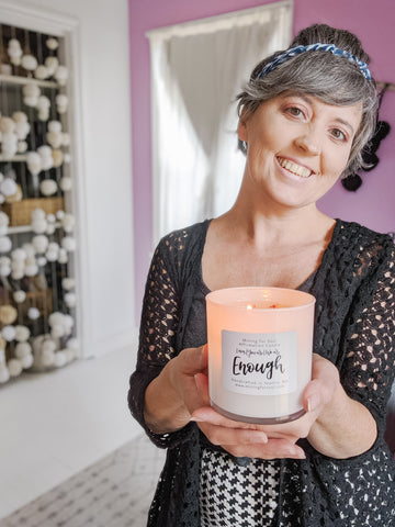 Smiling holding out a lit Enough affirmation candle | Mining For Soul
