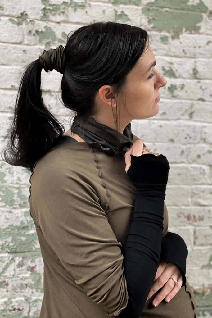 the band in olive secures ponytail with ore around the neck
