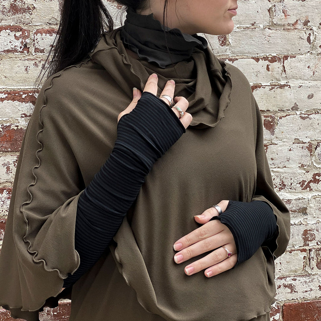 snuggle up in cozy subtle black opera sleeves peeking out from olive flirt poncho