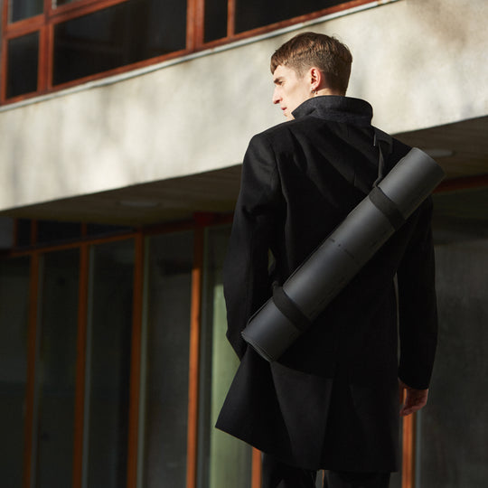 Gabriel carrying a Furö Studios design yoga mat with a Series 03 carrying strap
