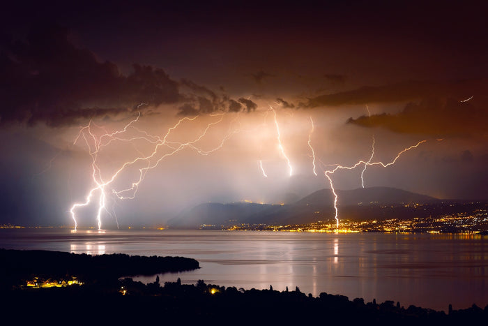 Different lightning bolts striking over the smooth water surface