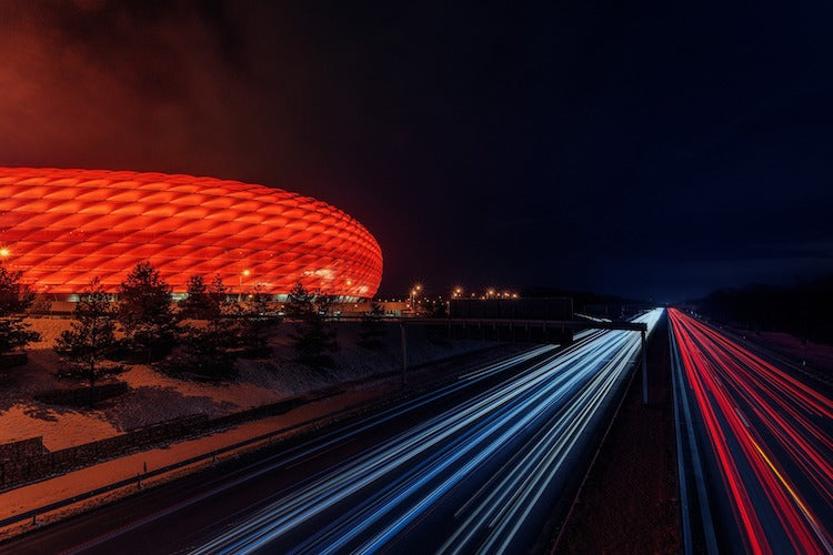 cars passing next to Allianz Arena at night