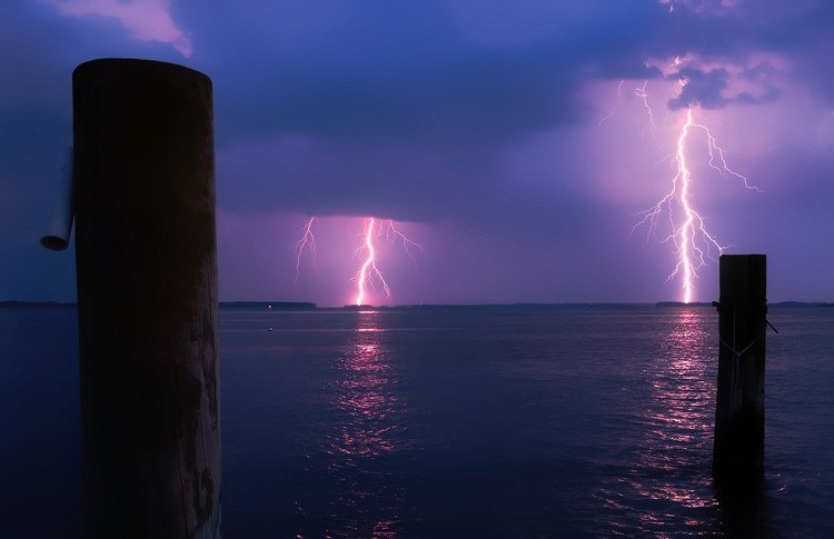 A purple lightning bolts strikes on the horizon and being photographed by Smart+