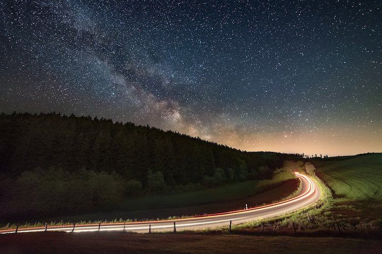 milky way and moving cars at night