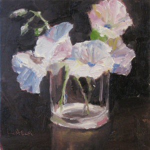 White flowers in a glass on a dark background.
