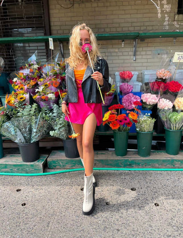 Girl in front of flower shop wearing custom orange and pink corset lace up top, piunk barbie mini skirt, leather jacket and boots