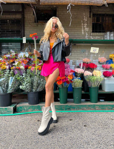 Liv wearing pink leg slit mini skirt with orange lace up corset and leather jacket in NYC outside a flower shop soho