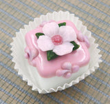 Pale Pink Primrose atop a Strawberry Petit Four Chocolate