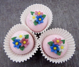 Three Flower Nosegay atop a Pink/White Petit Four Chocolate