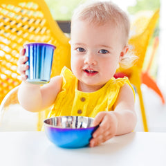 Adorable toddler girl using her Ahimsa stainless steel cup and bowl.