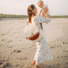Mom in floral dress wearing DUO Backpack lifting her baby in the air on the beach.