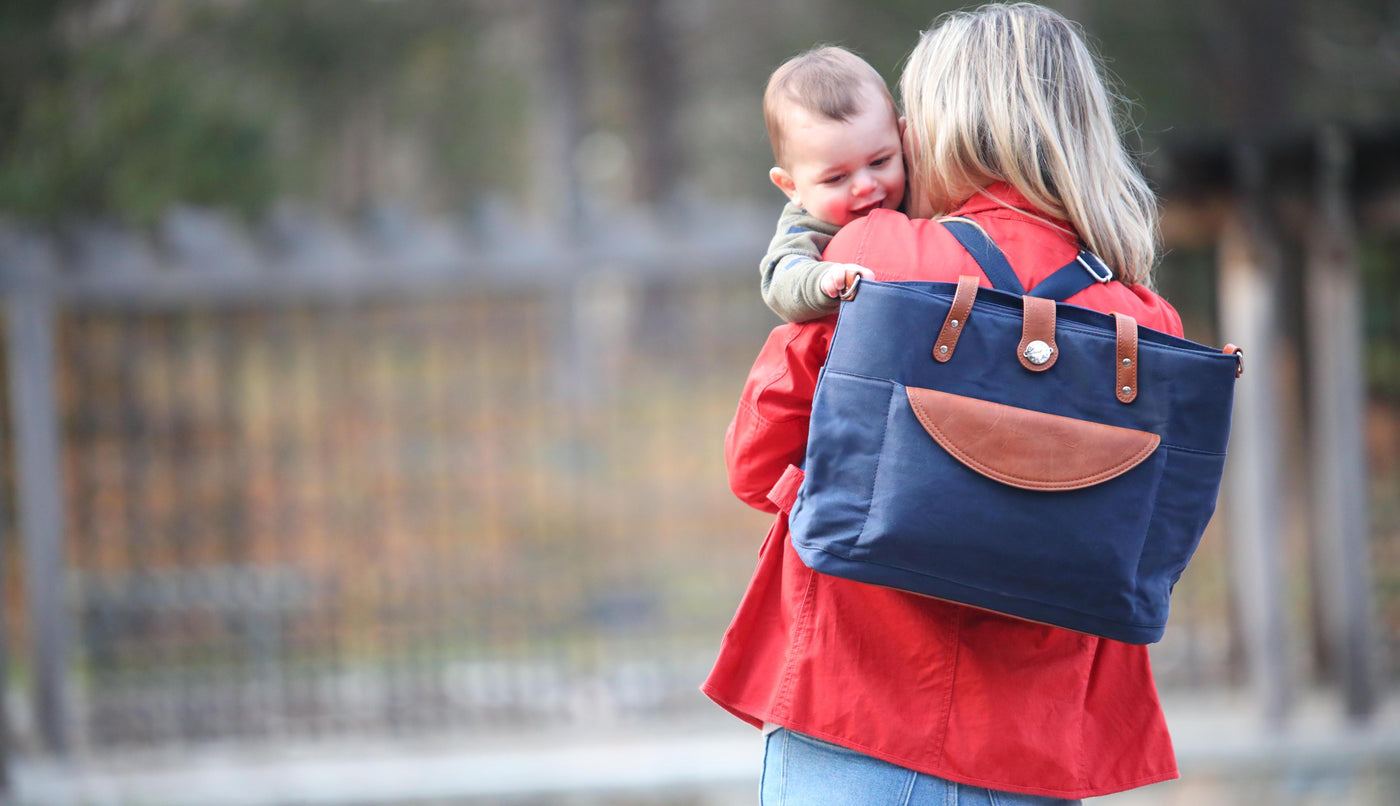 Mom holding baby over shoulder wearing navy blue waxed canvas backpack with brown vegan leather accents.