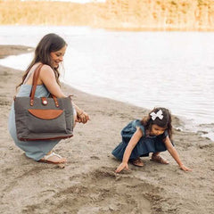 Mom with CarryAll Tote crouching on sandy beach with little girl playing.