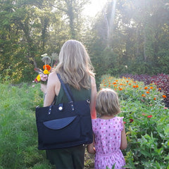 A mom and little girl take a stroll through a huge garden with flowers and vegetables on either side.