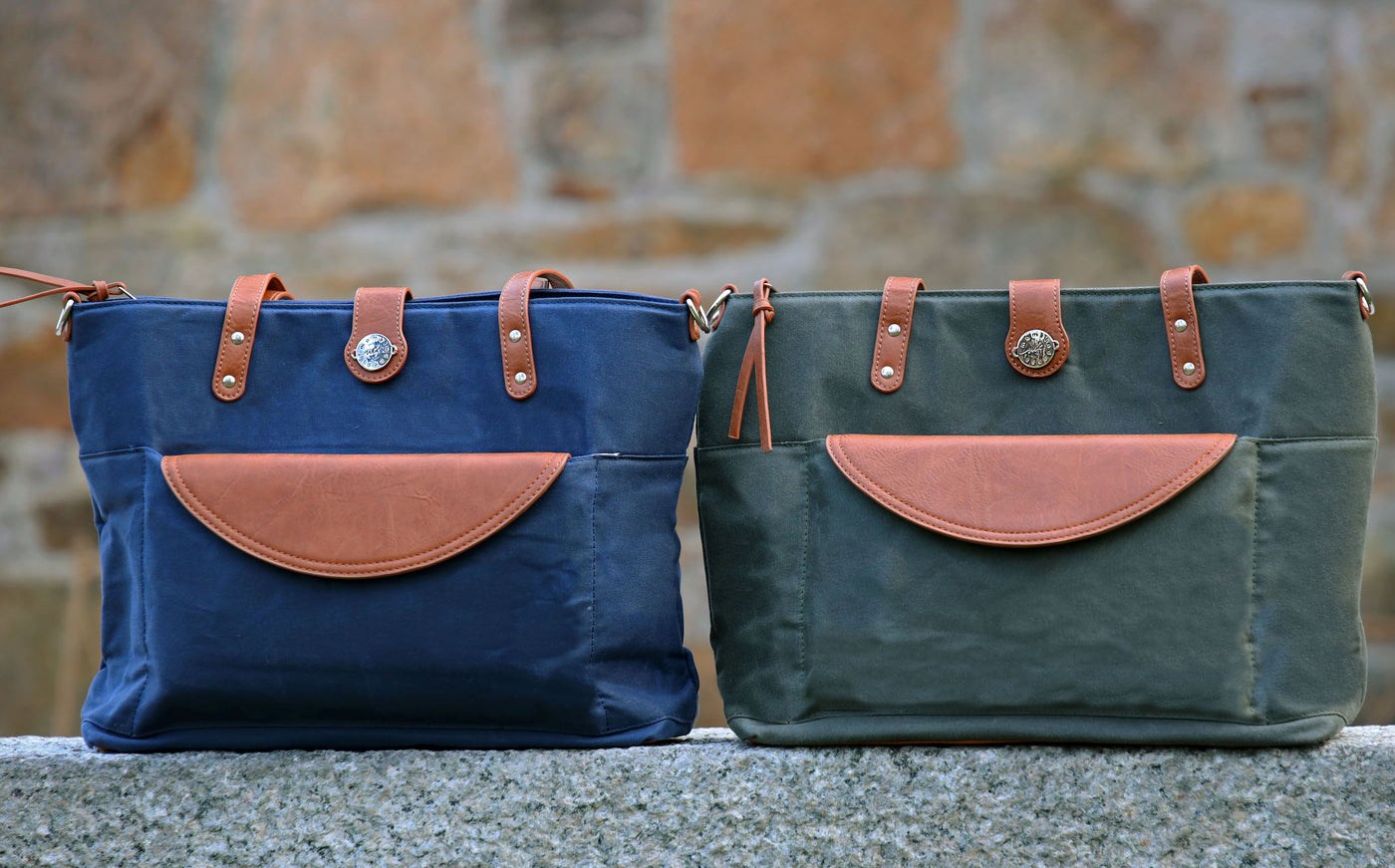 Group picture of navy blue & forest green waxed canvas totes with brown vegan leather accents sitting on a wall.