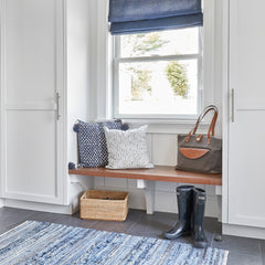 A mudroom bench with throw pillows, grey canvas CarryAll Tote, wicker basket and boots.