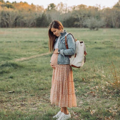 Woman wearing a DUO Backpack holding her pregnant belly, standing in field.