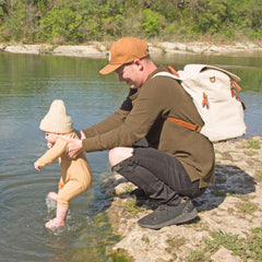 A dad crouched on a lake shore wearing a brown baseball hat and a beige backpack with brown vegan leather accents, holding his baby wearing a tan onesie and get and splashing his toes in the lake.