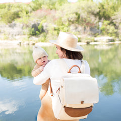 A mom in a white shirt and hat, wearing a beige backpack with brown vegan leather accents, holding her baby peeking over her shoulder and standing in front of a lake landscape.