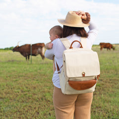 A mom in white shirt and tan hat wearing a beige backpack, holding a baby in her arms peeking over her shoulder, in front of a pasture with cattle.