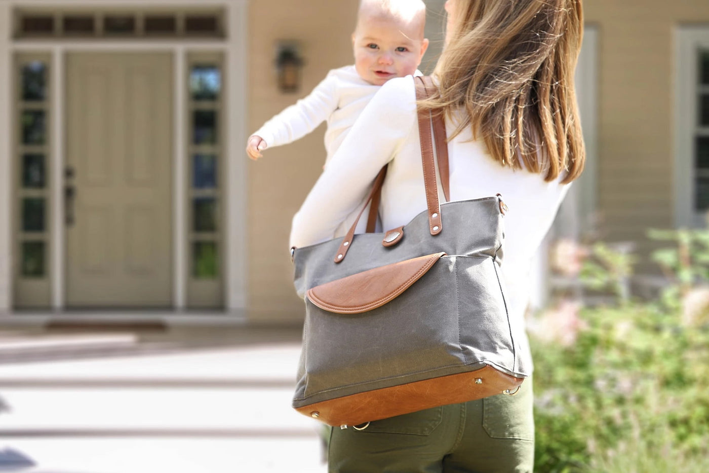 Mom carrying baby outside of home while wearing grey Carry All Tote Trio on her shoulder.