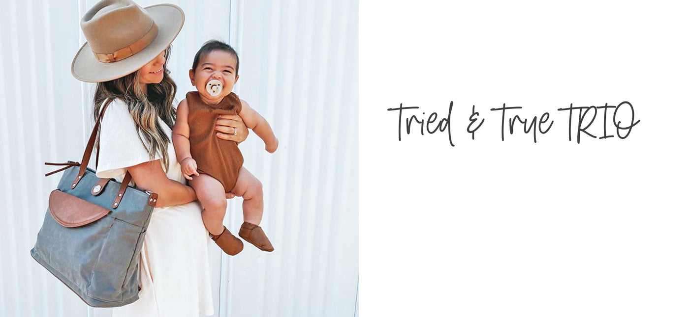 "Image of a mom in a white dress and tan hat wearing a grey waxed canvas & vegan leather carryall tote diaper bag on her shoulder holding her baby who is smiling with a pacifier. Copy overlay reads ""Tried & True TRIO"""