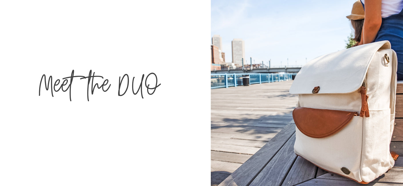 "Image of a stone colored canvas backpack diaper bag with caramel brown vegan leather accents, sitting on a bench by a pier. Copy overlay reads ""Meet the DUO""."