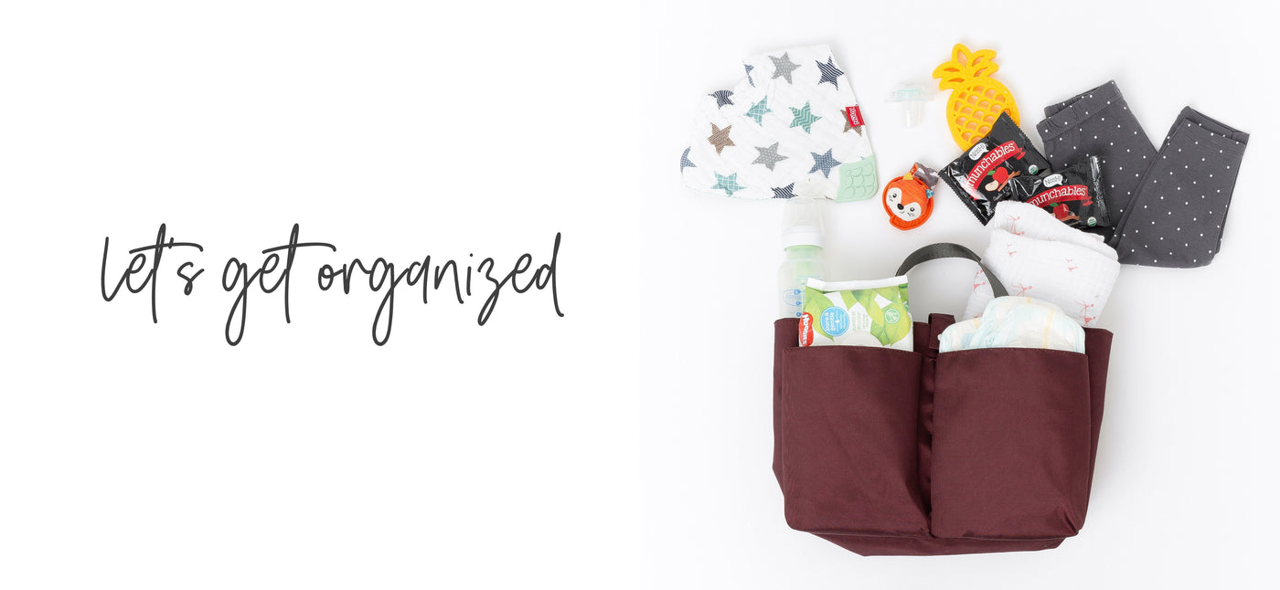 "A burgundy colored diaper bag organizer with 2 front pockets and gray carry handles, loaded with diapers and wipes and with other baby accessories laying outside on a white background. Copy overlay reads ""Let's get organized."""