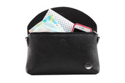 Black vegan diaper clutch shown open and filled with diapers, wipes, phone and changing pad.