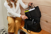 Woman sitting on bench placing filled black organizer filled with baby's items inside the Black Carry All Tote.