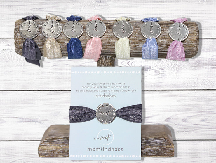 A 7-pack of stretchy hair ties in assorted colors, each with an engraved silver tone charm; perfect as baby shower favors.