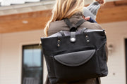 Black Carry All Tote Trio being worn as a backpack by mom carrying baby.