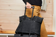Woman walking with Black Carry All Tote attached over handle of rolling suitcase via the trolley sleeve on back side of tote.