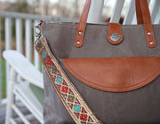 A bright color & gold shimmer patterned embroidered bag strap on a grey waxed canvas tote with brown vegan leather accents, hanging on the back of a white wooden rocking chair.