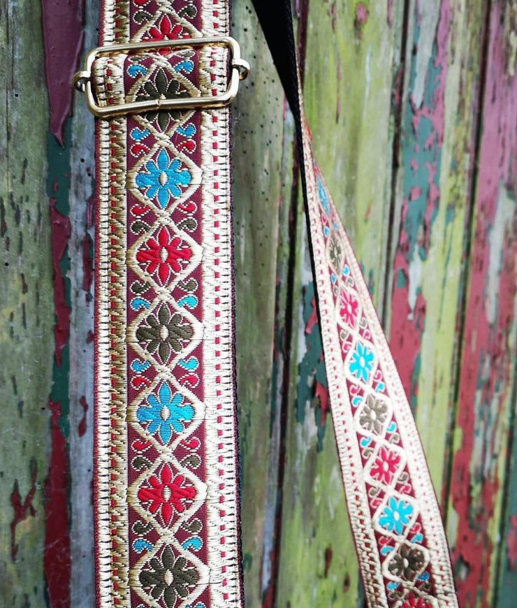 A close-up on a multi-color wood background of an adjustable length, embroidered bag strap with gold, green, magenta and blue diamond flower pattern and silver clasp.