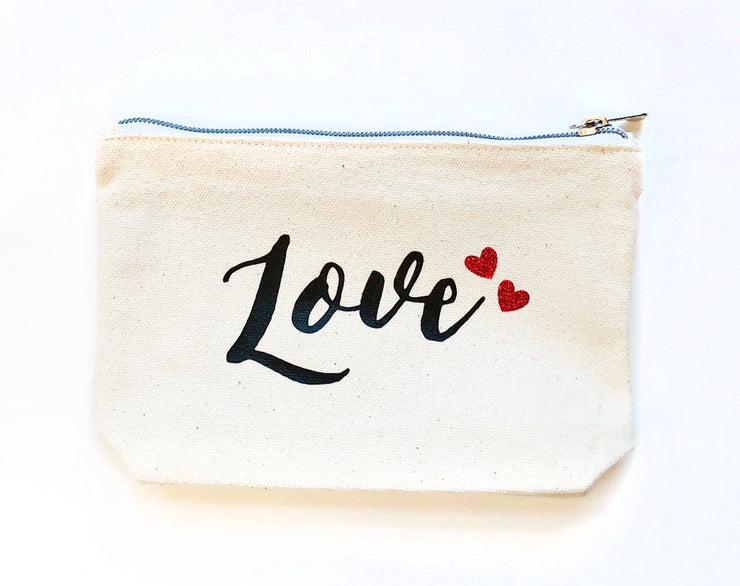 Ivory color zip-top canvas case with the word LOVE and two red hearts printed on front, laying flat on white background.