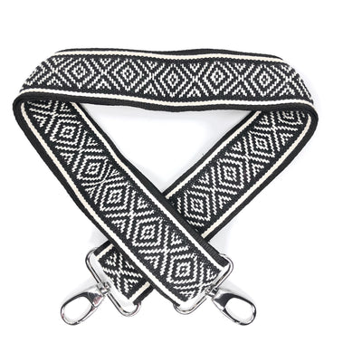 A black and white diamond patterned woven messenger strap with sliver-colored buckles, shown laying on a plain white background.