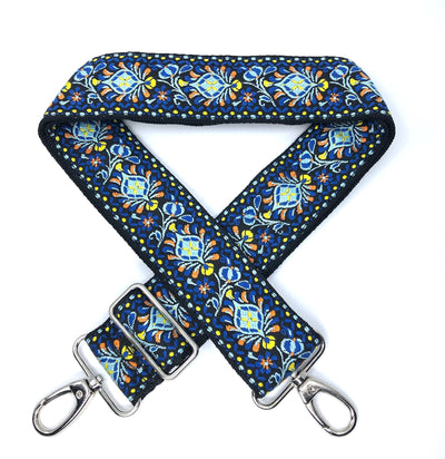 A blue jacquard woven adjustable messenger strap (accent colors of yellow and orange) with sliver-colored buckles, shown laying on a plain white background.