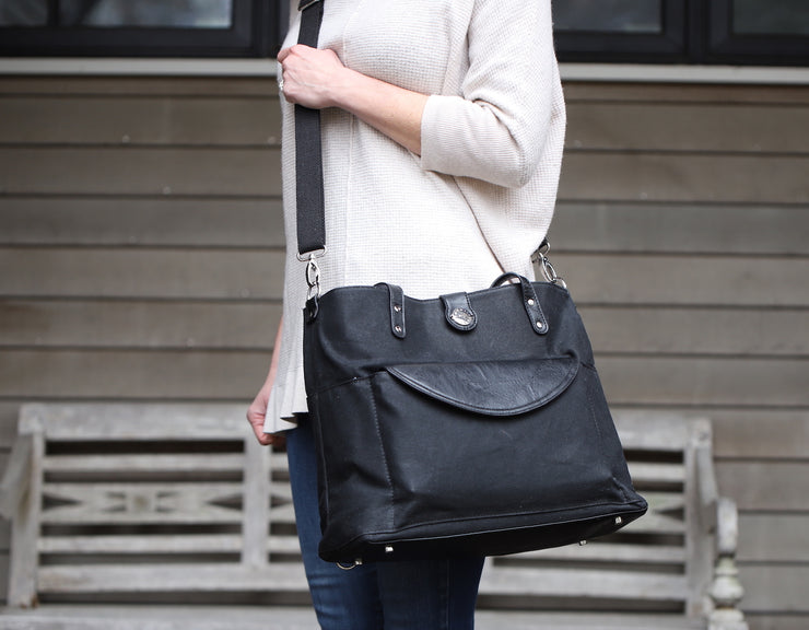 Black Carry All Tote Trio with vegan diaper clutch in front pocket of tote being worn crossbody with messenger strap by woman standing outside.