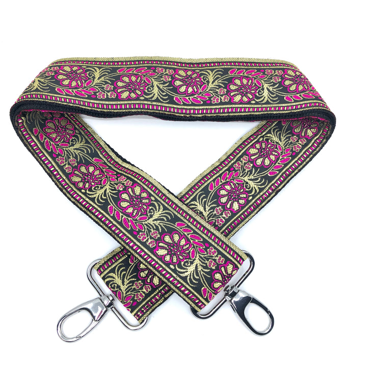 A close-up on white background of an adjustable length, embroidered bag strap with gold, magenta and black floral pattern and silver clasp.