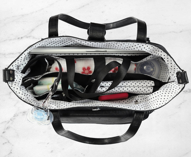 Top down view of interior of black Carry All Tote Trio, showing polka dot lining, laptop pocket and organizer packed with baby's items.